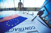 Contract with pen, touchpad, eyeglasses, American flag and that of European Union with businessman on background