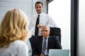 stock photo of 55-60 years old  - Three businesspeople having a meeting in the office with laptop computer on the desk - JPG