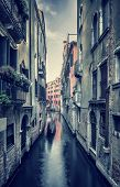 Grunge style photo of an old narrow Venetian street, beautiful aged buildings over water canal, romantic destination, Venice, Italy