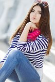 image of straight jacket  - Beautiful young girl, Caucasian appearance, with dark, long, straight hair, brown eyes and beautiful dark eyebrows, wearing a striped shirt, blue jeans, wearing pink neck scarf, sitting outdoors on stairs in the city. ** Note: Shallow depth of field - JPG
