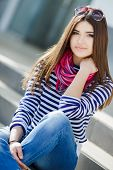 picture of pink eyes  - Beautiful young girl, Caucasian appearance, with dark, long, straight hair, brown eyes and beautiful dark eyebrows, wearing a striped shirt, blue jeans, wearing pink neck scarf, sitting outdoors on stairs in the city.