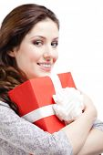 Young woman hands a xmas gift wrapped in red paper, isolated on white