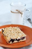 Homemade grated pie with jam and glass of milk on tablecloth and color wooden background