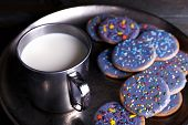 Glazed cookies on metal tray with mug of milk on rustic wooden planks background
