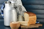 Retro can for milk with fresh bread and glass jug of milk on wooden background. Bio products concept