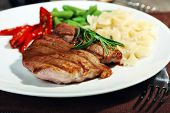 picture of plating  - Steak with vegetables and pasta on plate on wooden plate - JPG