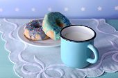 Glazed donuts with cup of milk on napkin and color dots background