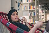 stock photo of turban  - Beautiful young brunette with turban drinking coffee in a bookstore - JPG