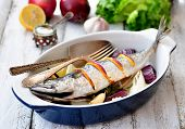 Fresh mackerel fish baked with a lemon, bow, salt and pepper on a wooden table