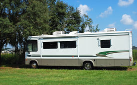 stock photo of snowbird  - RV parked in the shade of a tree - JPG
