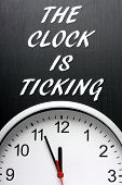 picture of midnight  - The phrase The Clock is Ticking in white text on a blackboard above a modern wall clock - JPG
