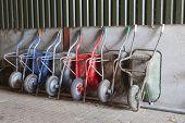 pic of wheelbarrow  - six old and rusty wheelbarrows rest against wall of farm barn - JPG