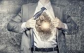 stock photo of heroes  - Young businessman in suit opening his chest and acting like super hero - JPG