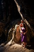 picture of cave woman  - woman and man kiss in cave at front sun rays