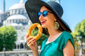 picture of bagel  - Young woman eating turkish bagel in Istanbul - JPG