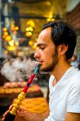 picture of shisha  - Man smoking turkish hookah in the cafe with coloful lamps on background in Istanbul - JPG