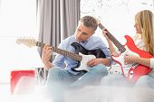 foto of father daughter  - Father and daughter playing electric guitars at home - JPG