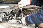 pic of overhauling  - Closeup of an auto mechanic working on a car engine - JPG