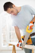foto of sawing  - Man sawing wood in new house - JPG