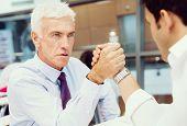 stock photo of wrestling  - Two businessmen competeting arm wrestling in office - JPG
