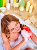 picture of bast  - Woman holding red wisp of bast and taking bath - JPG