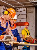 image of millwright  - Happy group people  builder with circular saw working indoor - JPG