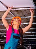 pic of suspenders  - Woman in builder uniform installing suspended ceiling - JPG