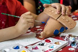 stock photo of pottery  - Children painting pottery at a workshop organized by the International Children - JPG
