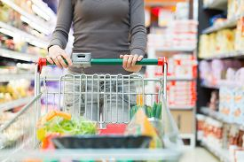 image of grocery cart  - Woman pushing a shopping cart in a grocery store - JPG