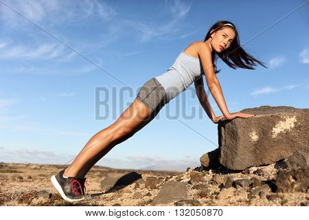 Strength training fitness woman working out core with angled pushups or planking on rock. Asian athl