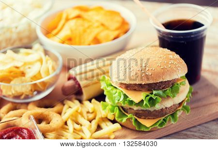 fast food and unhealthy eating concept - close up of hamburger or cheeseburger, deep-fried squid rin