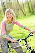 Beautiful young woman relaxing after riding a bike