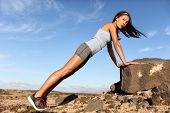 Strength training fitness woman working out core with angled pushups or planking on rock. Asian athl poster