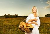 picture of household farm  - Beautiful young woman with a basket full of fresh baked bread - JPG