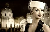 Beautiful young woman drinking coffee. Old city background behind her