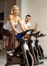 stock photo of exercise bike  - Group Of People Doing Exercise On A Bike In A Gym - JPG