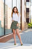 Young fashion woman standing at the window in a city street. Stylish female model in white short and poster