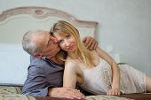 Beautiful Young Woman With Her Senior Lover Lying On The Bed. Man Kissing His Girlfriend.portrait Of poster