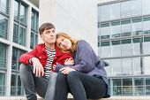 Young Affectionate Heterosexual Couple Sitting On Steps In Front Of Modern Building With Glass Facad poster