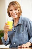 image of mature adult  - Mid age woman drinking orange juice - JPG