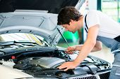 Car mechanic working in car service workshop poster
