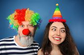 Young woman and mature man in funny disguise on color background. April fools day celebration poster