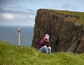 Woman sitting in grass on cliff of the island of Mykines, Faroe Islands