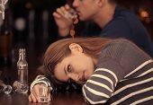 Young woman with empty glass lying on bar counter. Alcoholism problem