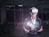Earth globe against an old man using a virtual reality headset