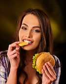 Woman eating piece of cheese and hamburger. Portrait of student consume fast food on table. Girl try poster
