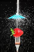 Sweet juicy strawberry on a fork protected from a stream of falling sugar.  Sugar-free concept.