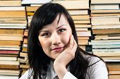 Young Student Thinking Against Piled Up Books