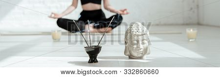 poster of Cropped View Of Woman Sitting In Half Lotus Pose Near Buddha Head Sculpture, Aromatic Sticks And Can