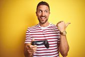 Young handsome man playing video games using joystick game pad over yellow background pointing and s poster